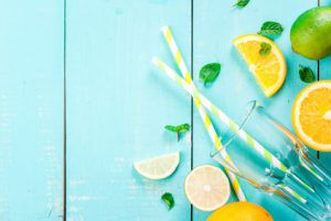 Ingredients for citrus juice or a refreshing summer cocktail: orange, lime, mint leaves, along with a glass and drinking straws, top view, copy space