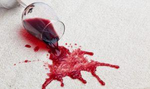 Ein umgefallenes Glas mit Rotwein verschmutzt einen Teppichboden.