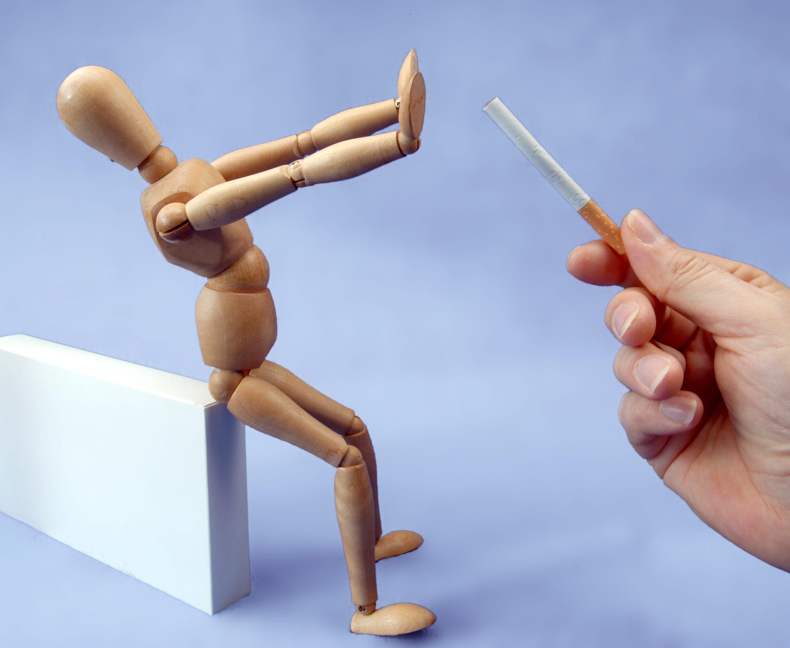 Holzfigur an Kante sitzend lehnt von Menschenhand gereichte Zigarette vehement ab